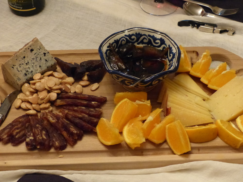 Blue cheese (such as Cabrales, Valdeon, Stilton or Gorgonzola).  Add nuts, date loaf, figs in syrup, oranges.