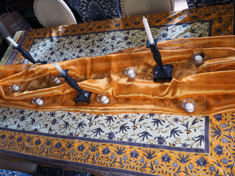 Tablecloth stretching full length of the table with an orange organza swath.