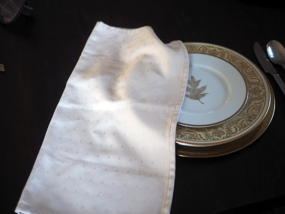 Fold napkin in half, then half again, than half yet again.