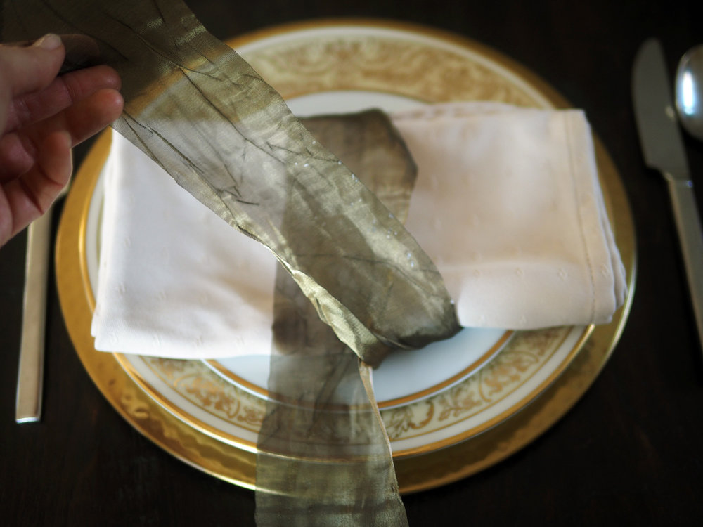 The top portion of the ribbon rests across the middle of the napkin while the bottom/under portion gets crossed over front.