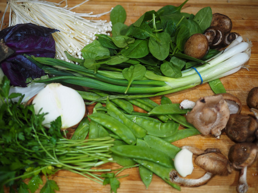 From the top left: Enoki mushrooms, spinach, Cremini mushrooms, scallions, Shitake mushrooms, garlic, snow peas, parsley, onion, red cabbage (which at the last minute I opted not to include), and savory cabbage which seemed to be camera shy and slipped out of the shot.