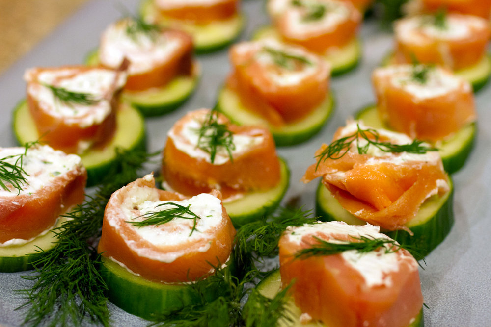 Salmon / cream cheese roll up a top a cucumber slice.