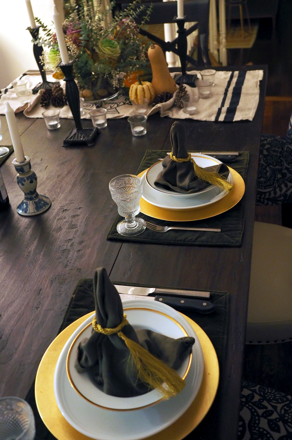 Table setting with green velvet placemats, gold chargers, white plates and a soup bowl with gold trim.