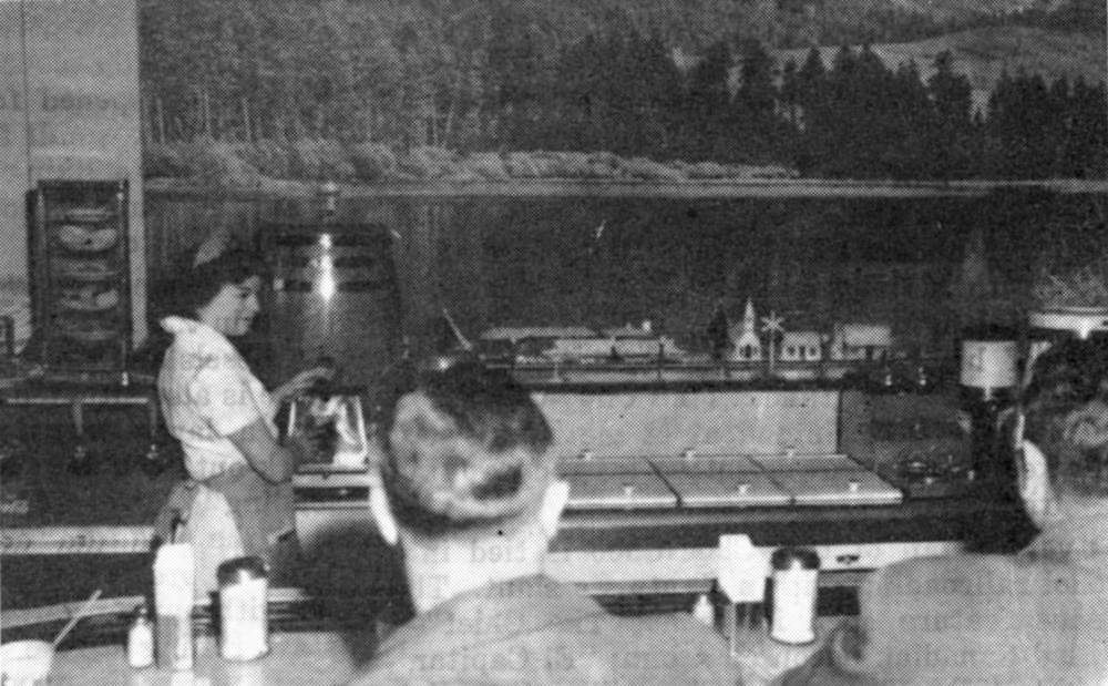 "Against the background of a huge photo-mural, Jessie Palmer, one of the Choo-Choo's waitresses, draws a coke for a customer as the miniature Santa Fe diesel hauls a load of ""empties"" back to the kitchen for more orders."