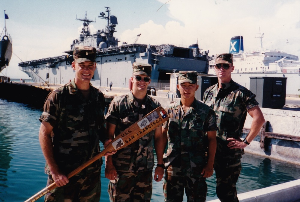 CMO Kurt Kane (far left, holding oar) stands with fellow lieutenants from the 4th Infantry Division at Guantanamo Bay Naval Station.  The oar he is holding was their unit symbol.""