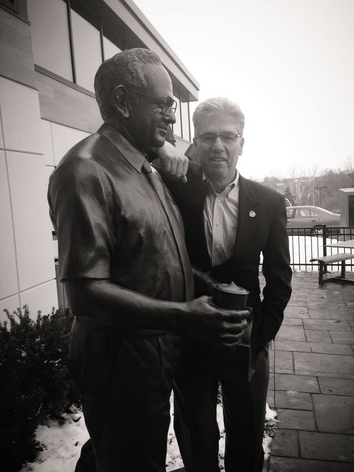 Denny poses by a statue of Dave at the opening of Wendy's Flagship restaurant in December 2013.