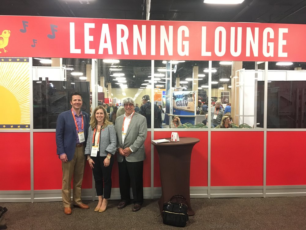 Carl, Liliana and SVP of Quality Assurance Dennis Hecker Pose Beside the Learning Lounge on NCBA's Trade Show Floor