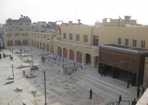 Bird's-eye view of the plaza showing the adjacent retractable theater. لقطة علوية للساحة تبين واجهة المسرح القابلة للفتح
