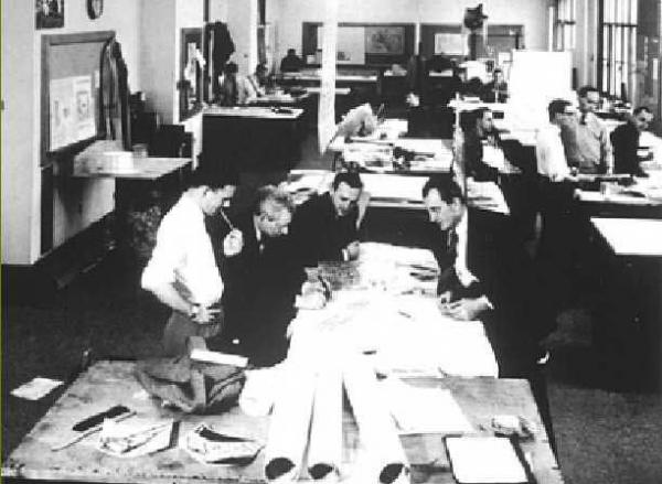 Figure 2: An MIT architectural design studio from c. 1960 showing Louis Kahn (second from left) giving a desk crit.