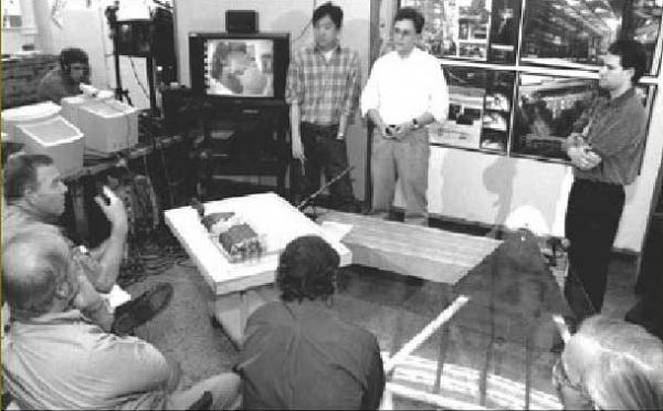 Figure 13: An MIT architectural design jury in which a remote juror (shown on the television screen) is participating through the aid of teleconferencing technologies.