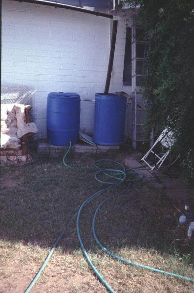 Figure 1: Collection of graywater from an indoor washing machine and rainwater from the roof into two connected barrels that feed a garden through hoses.