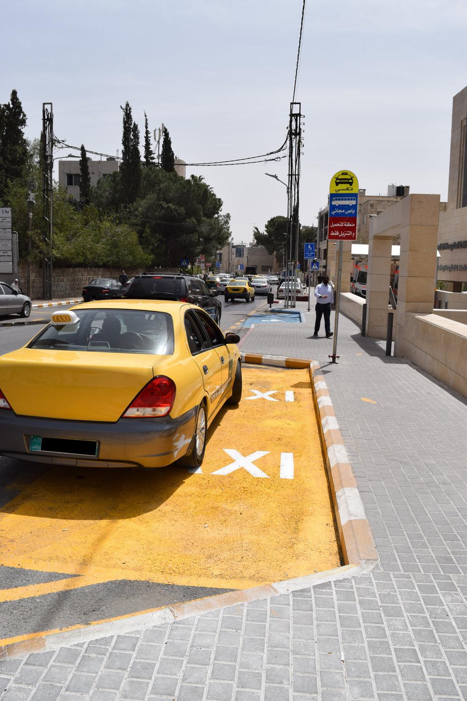 سيارة تكسي متوقفة في المكان المخصص لسيارات التكسي، ولكن جزءاً منها المتوقفة يمتد ليأخذ حيزاً من الشارع نفسه.