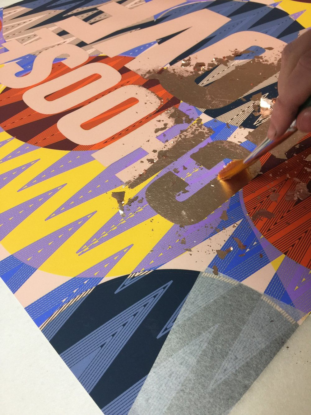 The foil being applied to screen printed glue, with a paint brush.