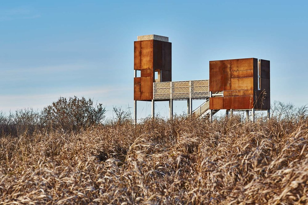Conceptually, the observation platform represents the singular cultural heritage—ethnic, linguistic and geographical—of dual origins. Floating over the landscape, the structure is comprised of two CORten steel bodies connected by a stage.