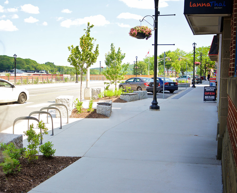 Trees soften the streetscape and provide shade for the granite benches that provide seating along the storefronts.