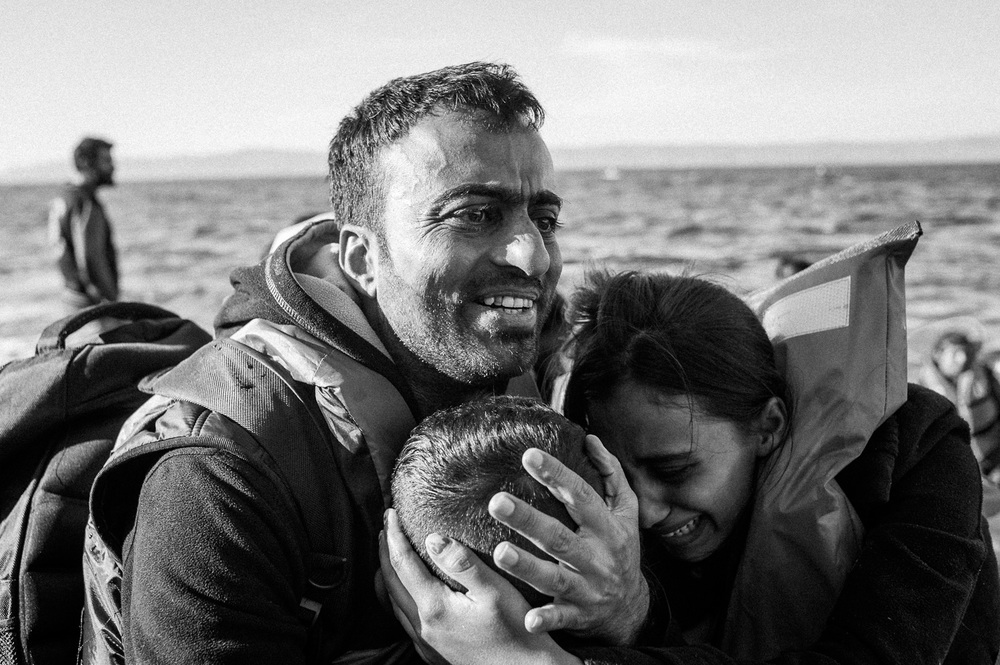 A Syrian refugee Sayid embraces his family after their overcrowded raft landed at a rocky beach in the Greek Island of Lesbos.