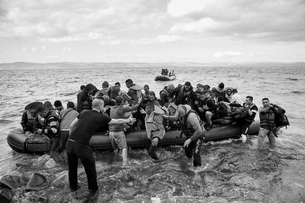 Migrants jump ashore after making the crossing from Turkey to the Greek island of Lesbos.