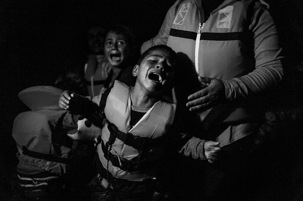 A boy is overcome with emotion as he comes ashore over the night, after making the crossing from Turkey to the Greek island of Lesbos.