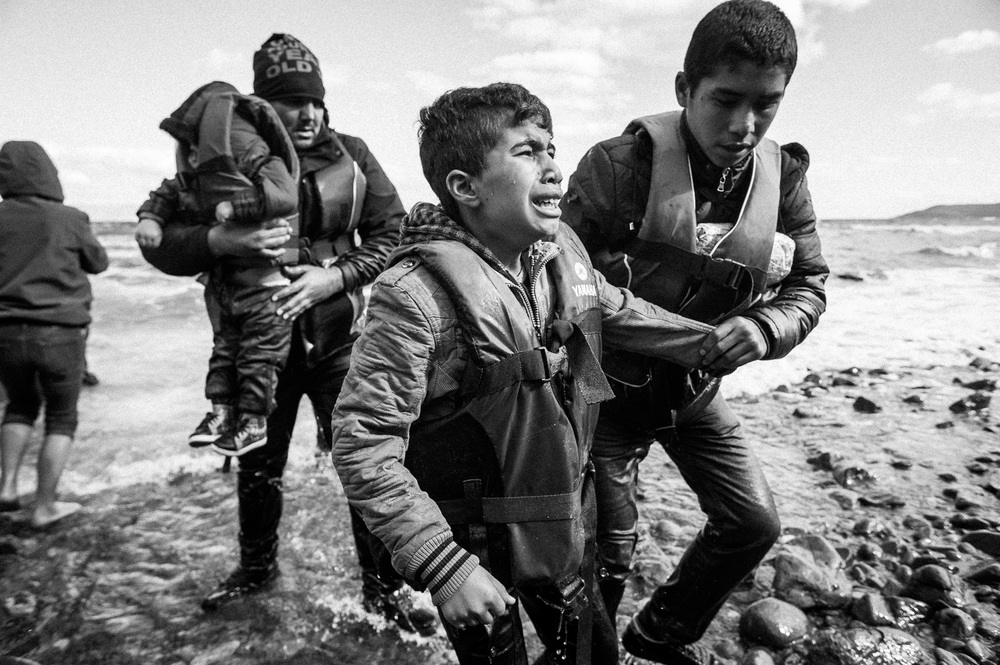 A boy is overcome with emotion as he comes ashore after making the crossing from Turkey to the Greek island of Lesbos.
