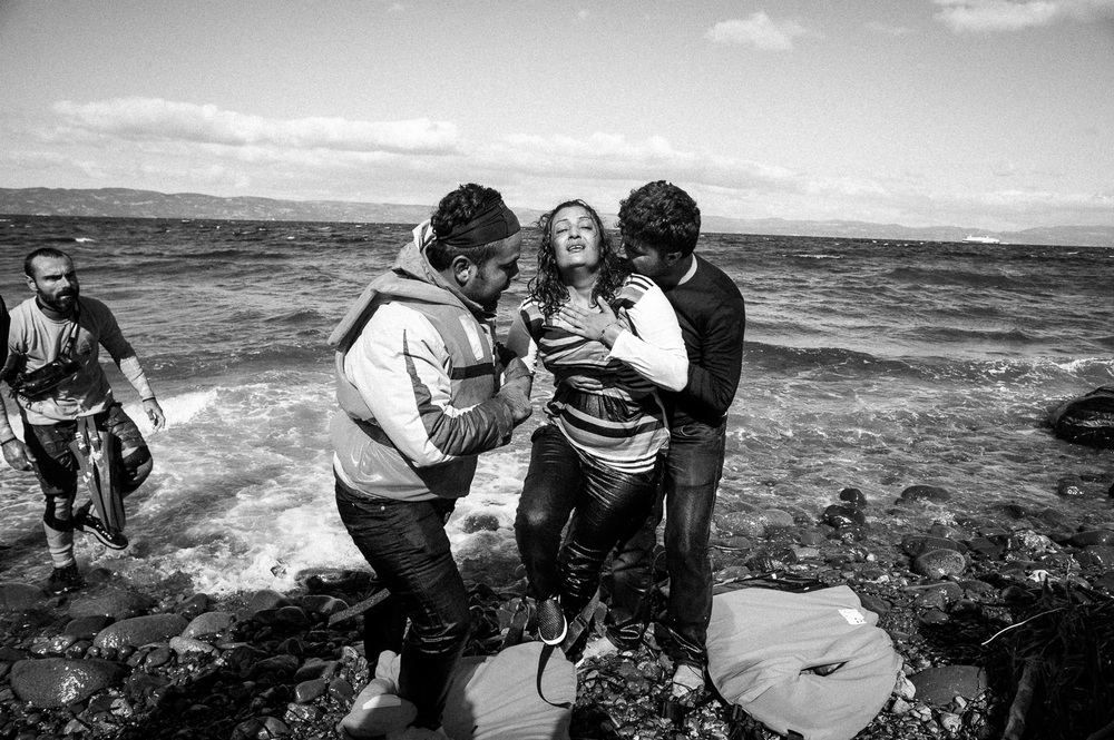 Distressed woman is helped ashore after making the crossing from Turkey to the Greek island of Lesbos.