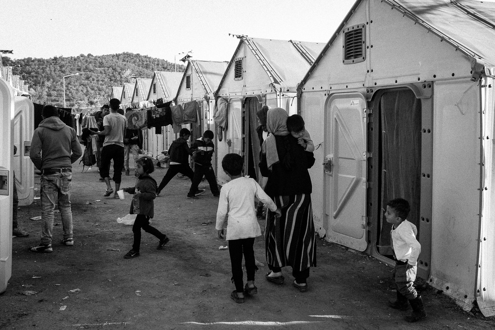 Refugees and migrants spend the night in a camp outside a processing centre in Moria.