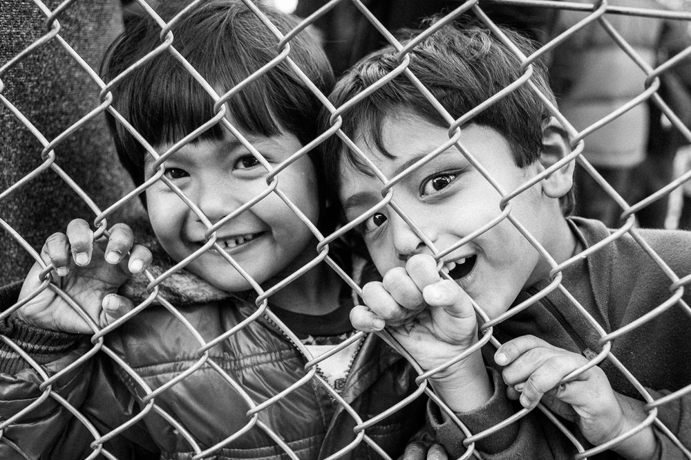 Children refugees looks through a fence at the Moria processing centre on the Island of Lesbos.