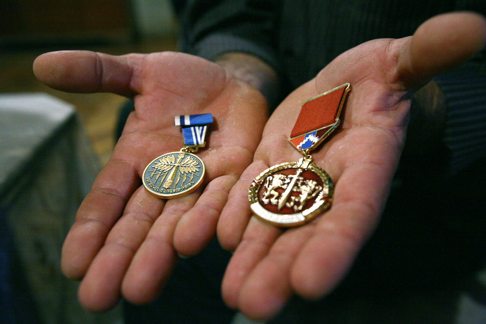 Garnik Arustamyan shows honorary medals received for his participation in Nagorno-Karabakh war.
