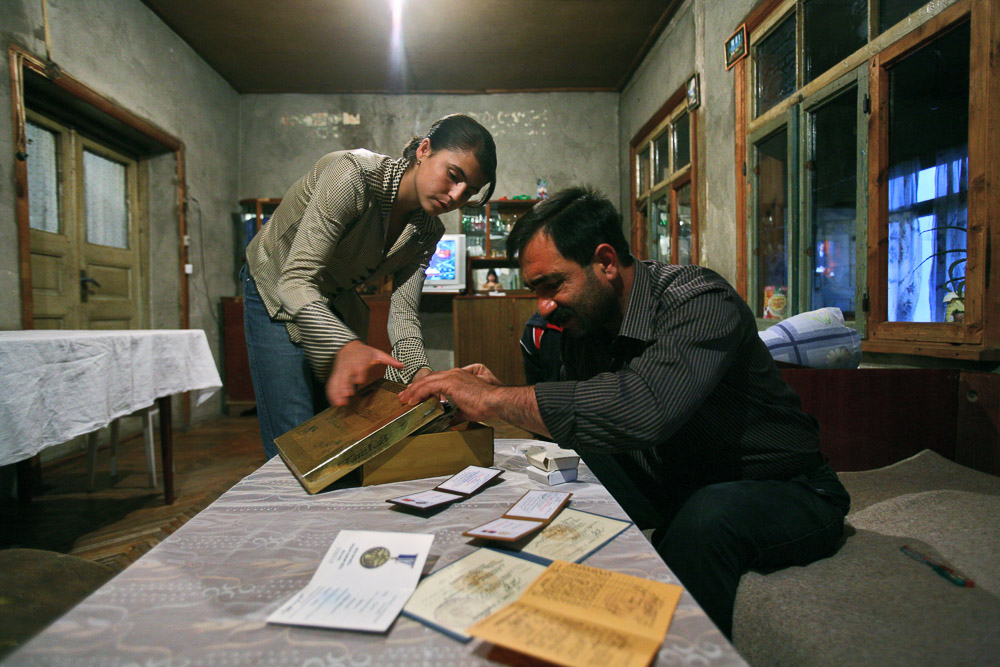 Garnik Arustamyan and his elder daughter, Alisa (age 15), search in a box for honorary distinctions received by Garnik for his participation in Nagorno-Karabakh war.