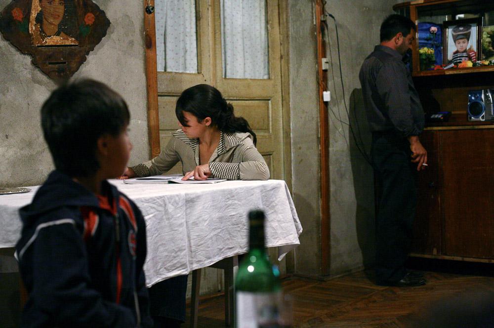 Alisa Arustamyan (age 15, center), the elder daughter of Garnik Arustamyan writes her homework in her family house in Shushi.