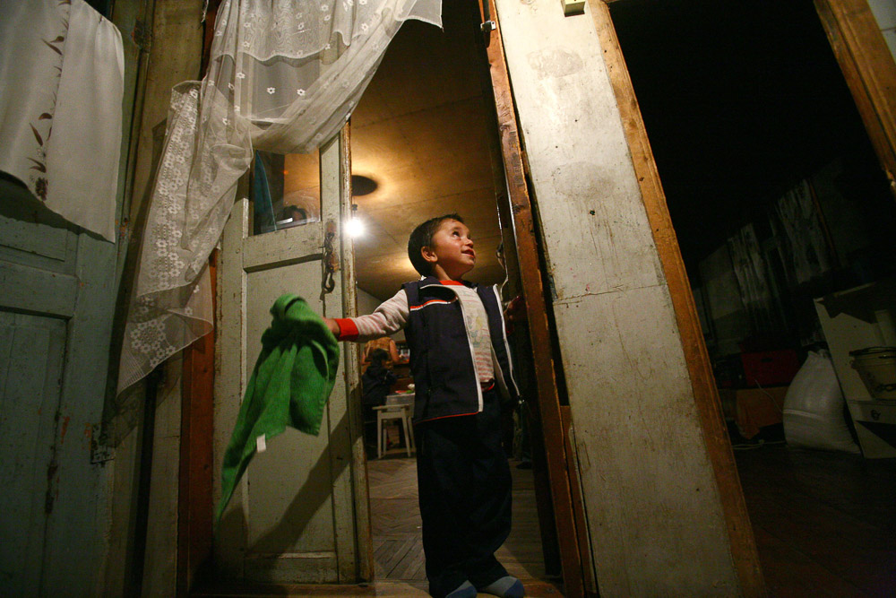 Arnold (age 4), the son of Garnik Arustamyan tries to hang the towel in a nail in the family house in Shushi.