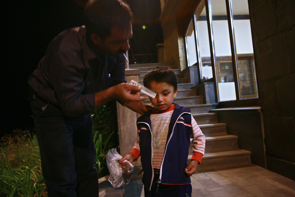 Garnik Arustamyan brushes the hair of his son Arnold (age 4) before he enters the night shift at his workplace, Shushi Revival Fund Organisation in Shushi.