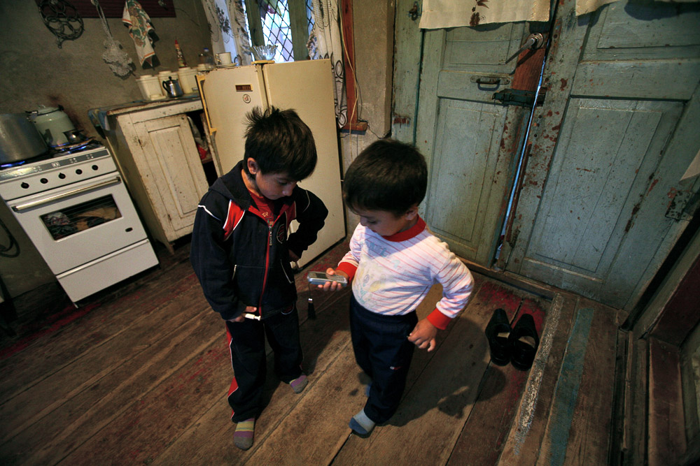 The two youngest children of Garnik Arustamyan, Haikuhi (age 6, left) and Arnold (age 4, right) are playing with a mobile phone in their house in Shushi.