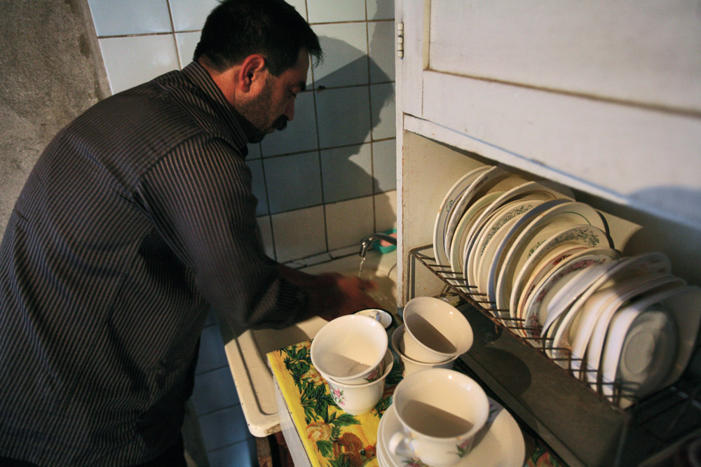 Garnik Arustamyan washes his hands after he worked in the backyard of his house in Shushi.