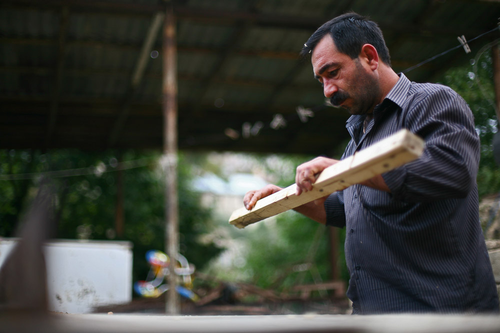 Garnik Arustamyan makes furniture in the backyard of his house in Shushi.