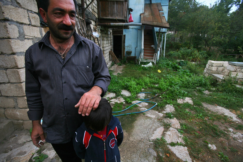 Garnik Arustamyan and his daughter Haikuhi (age 6) are standing in the backyard of their house in Shushi.