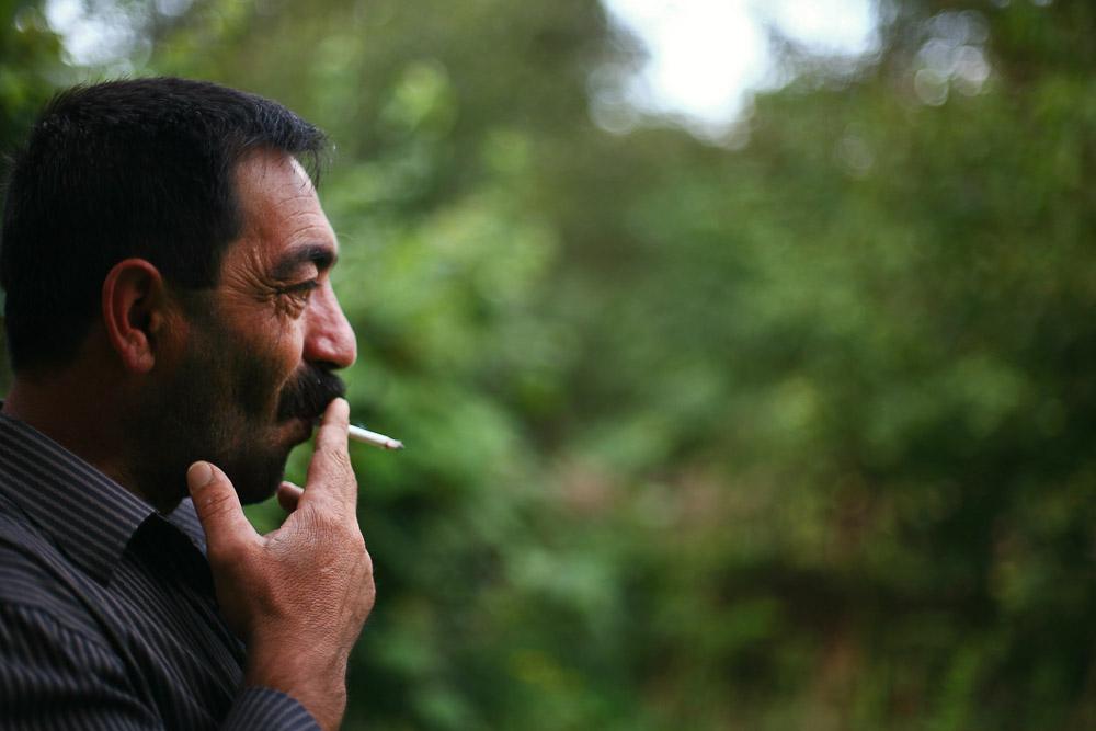 Garnik Arustamyan smokes a cigarette in the backyard of his house in Shushi.
