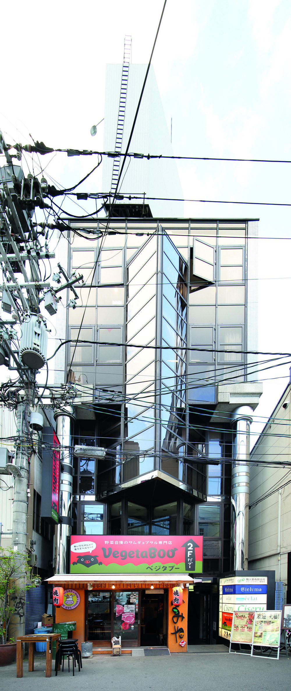 Image 3 / Any base building may have several of these scaffold extensions or entrances. Two modern pencil buildings and their add-ons, Bakuromachi and Dōtonbori, Osaka, Photograph by CC Williams