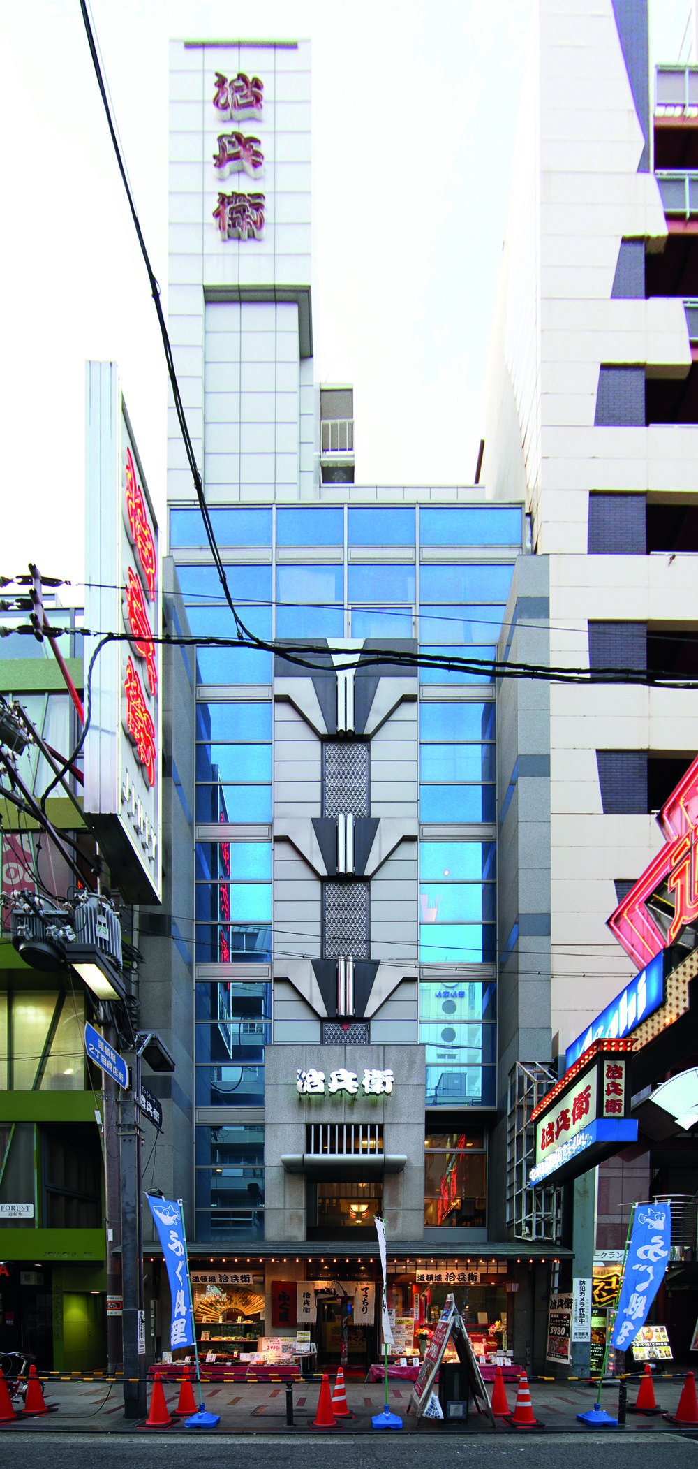Image 4 / Any base building may have several of these scaffold extensions or entrances. Two modern pencil buildings and their add-ons, Bakuromachi and Dōtonbori, Osaka, Photograph by CC Williams