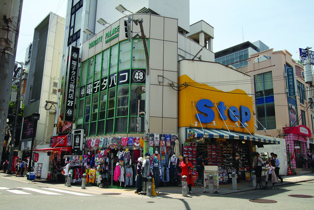 Image 11 / Many shops have little space inside: they're more like glorified storage cupboards. The major display hangs off the façade and over the sidewalk, Amerika Mura, Osaka, Photograph by CC Williams