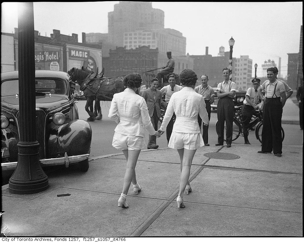 "Women in shorts cause car to ""crash"" into pole, Toronto, 1937. Photograph by Alexandra Studio"