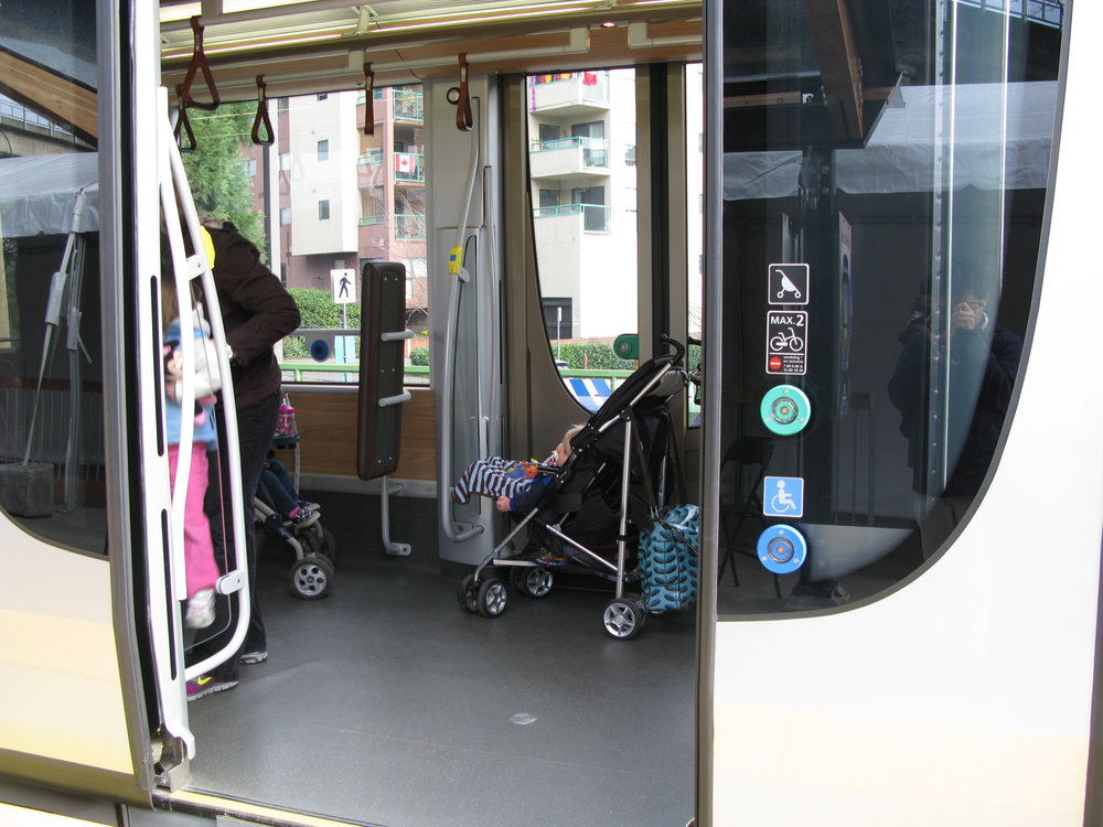 Child in stroller on Bombardier train. Photograph by Oran Viriyincy