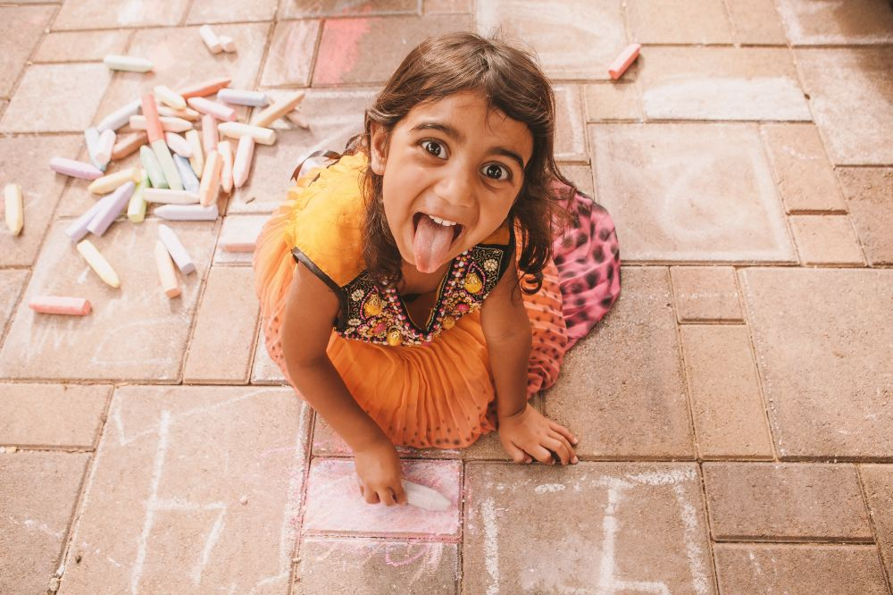 san   diego wedding photographer | child looking up with tongue out while drawing   with chalk