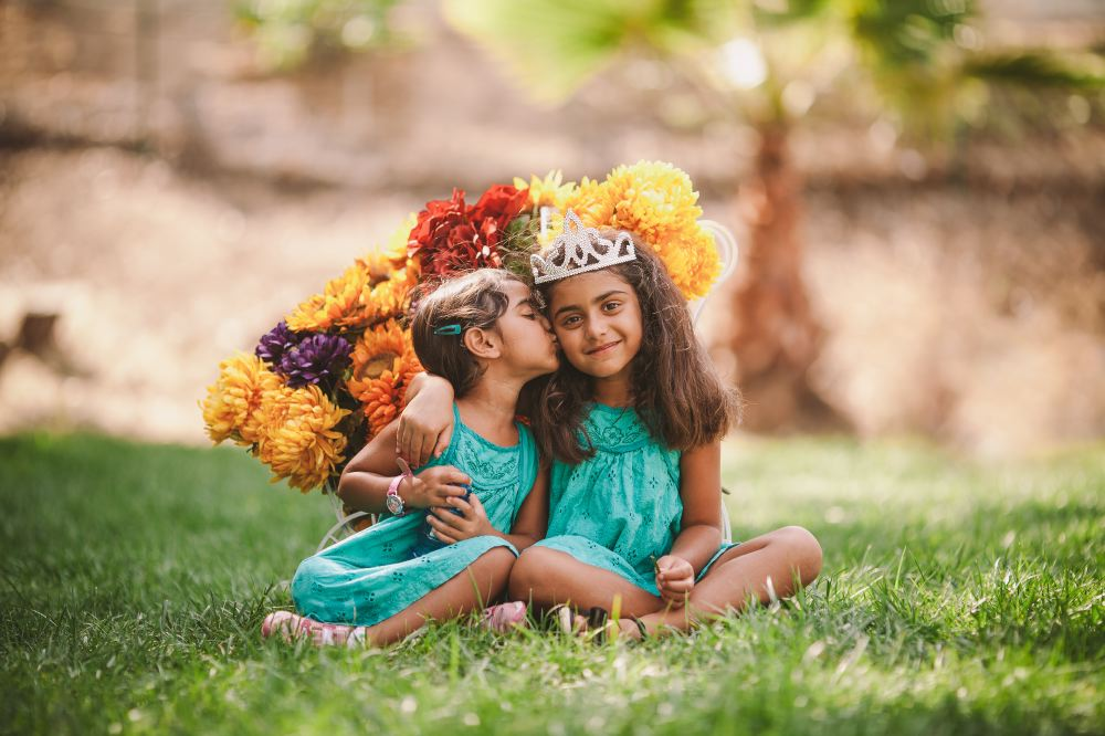 san   diego wedding photographer | children in tiaras and teal dresses with bunches   of flowers behind them
