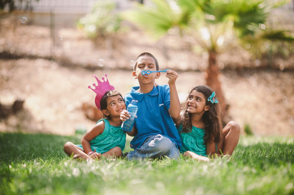 san   diego wedding photographer | kid blowing bubbles with 2 children looking and   smiling