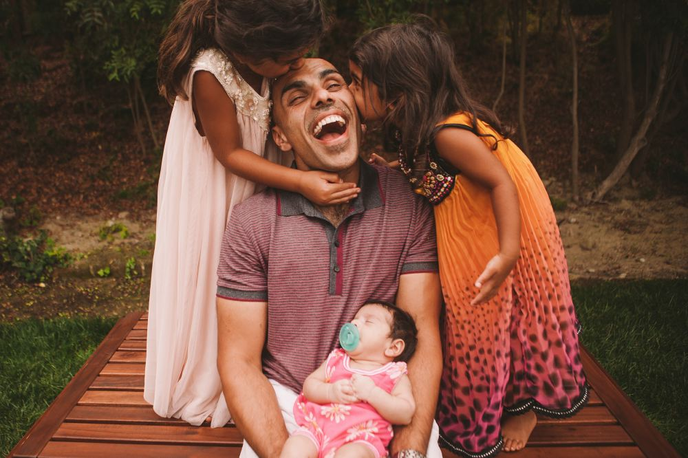 san   diego wedding photographer | man smiling with 2 kids kissing him on the head   and cheek
