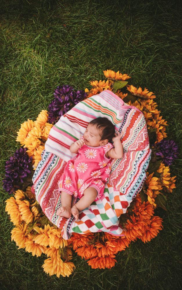 san   diego wedding photographer | child on the ground laying on a blanket   surrounded by flowers