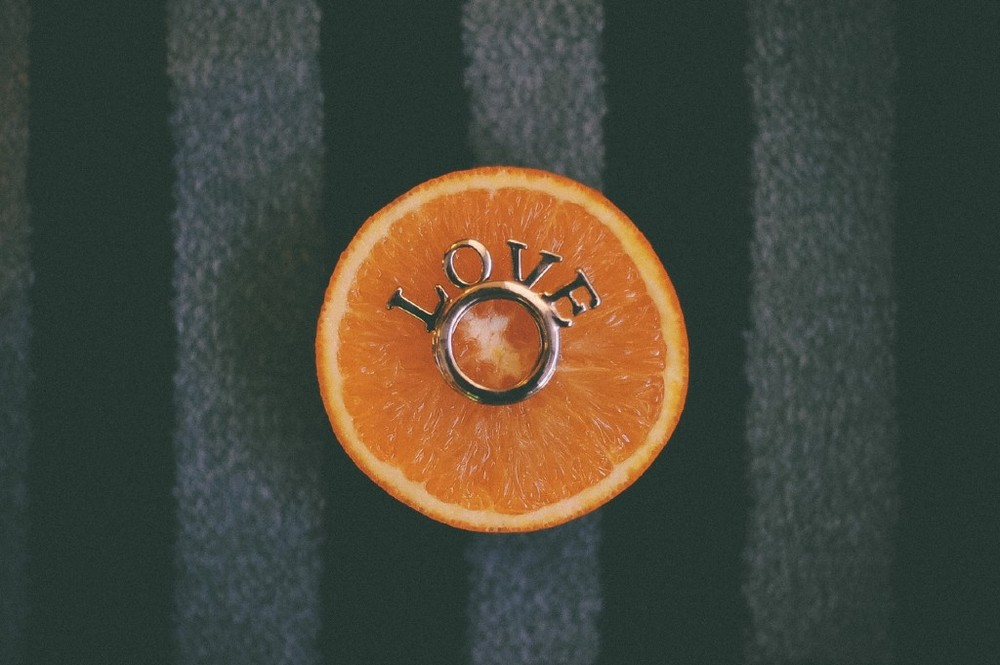 san   diego wedding photographer | ring with the word love on it on top of orange   half