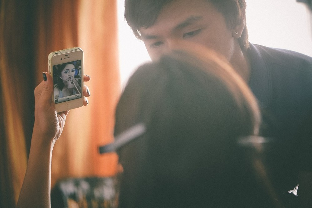 san   diego wedding photographer | woman holding up phone with makeup being done