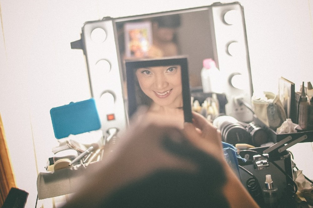 san   diego wedding photographer | woman smiling at mirror with makeup supplies in   front of her