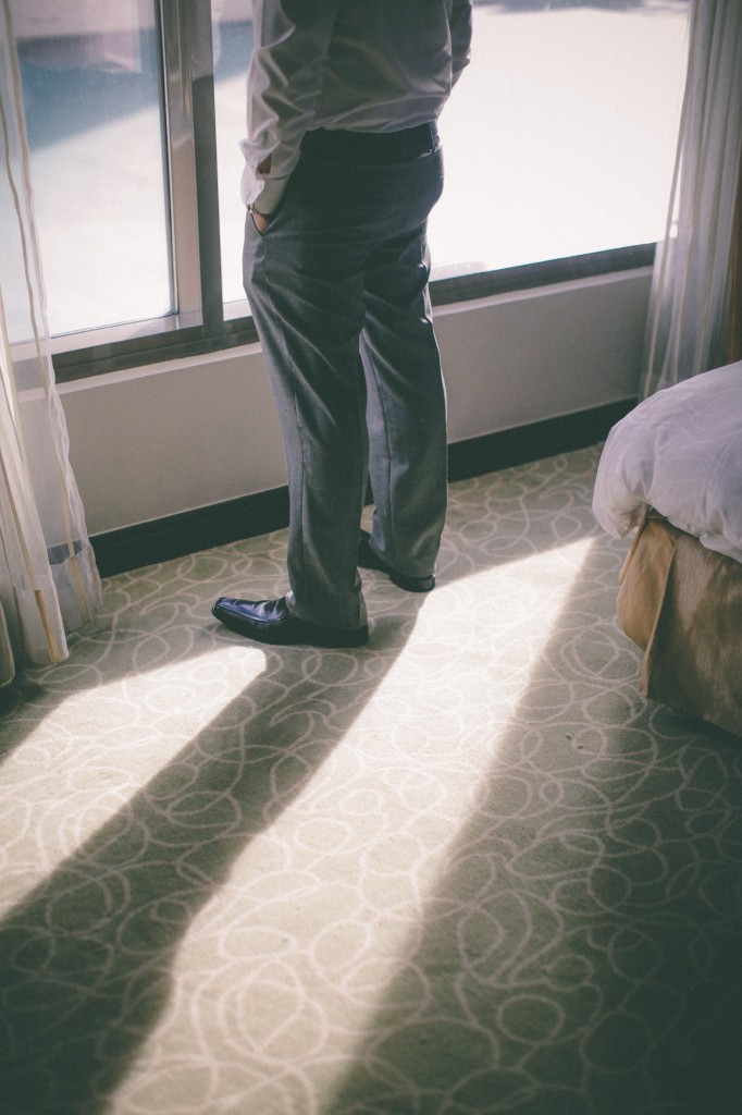 san   diego wedding photographer | lower body of man with hands in pocket looking   out window